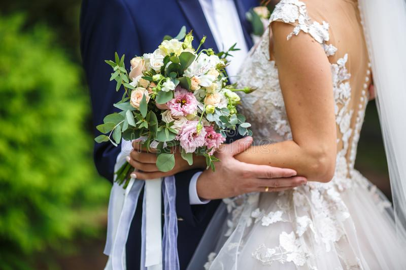 The bride put her hands on the shoulders of the bridegroom. bride with a bouquet of pink and white roses hugs and kiss the groom royalty free stock photos
