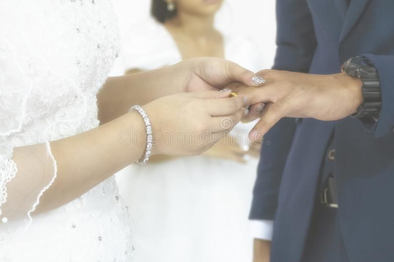 Bride Put the Wedding Ring to Her Groom in the Wedding Ceremony. Vintgae Style Picture with Gain Added royalty free stock photography