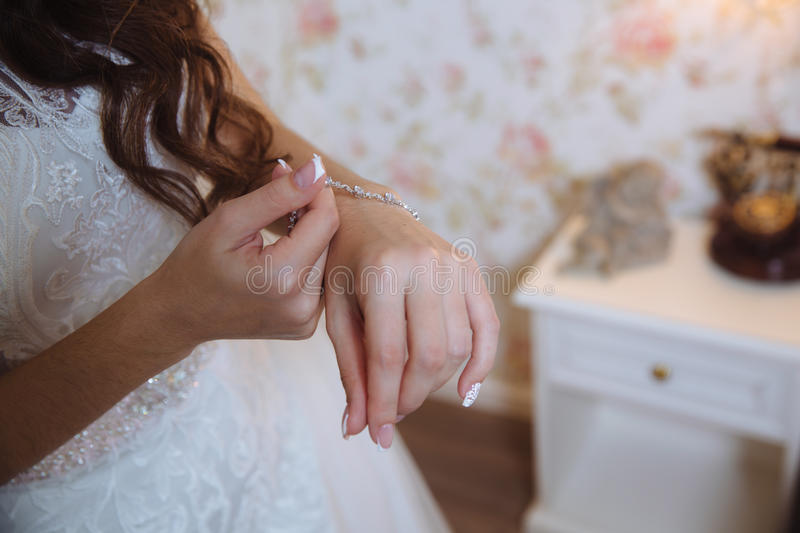 The bride puts the bracelet on her arm, close up.  royalty free stock images