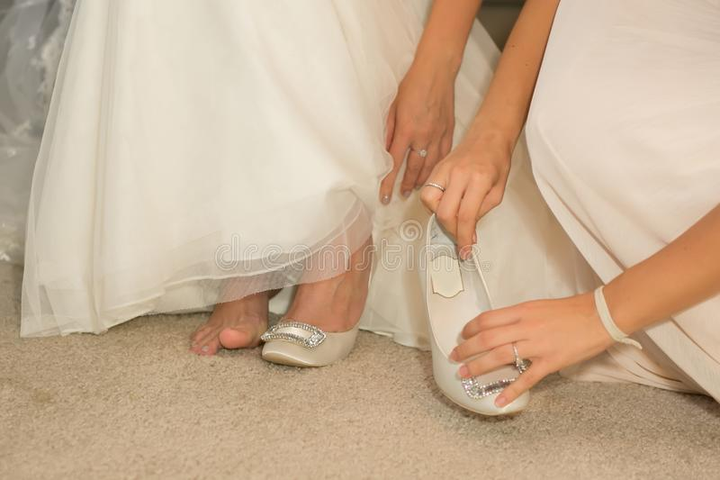 Bride puts on her wedding shoes in natural sunlight.  stock photos