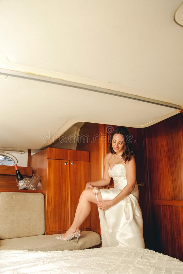 A bride puts the league in the cabin of a sailboat royalty free stock photos