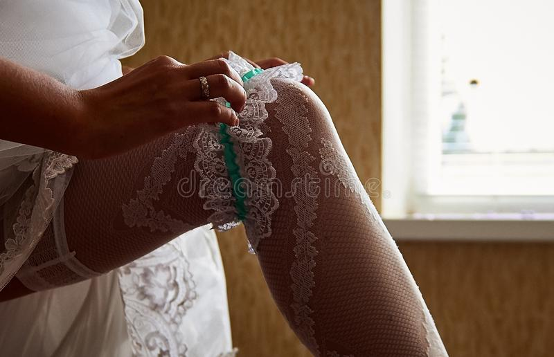 Bride puts on a wedding garter. Close up hands of bride putting on beautiful white garter royalty free stock images