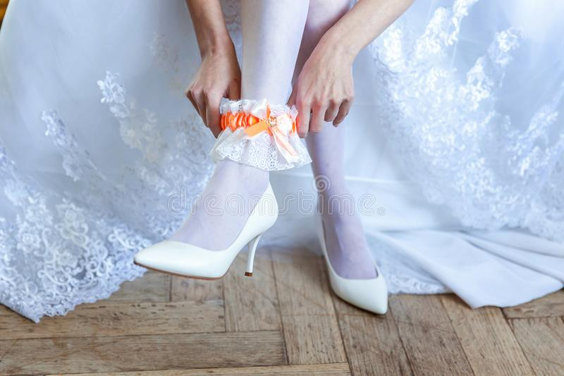 The bride putting on garter. Garter on the leg of a bride, slim bride in wedding luxury dress showing her silk garter. woman have a final preparation for wedding royalty free stock images