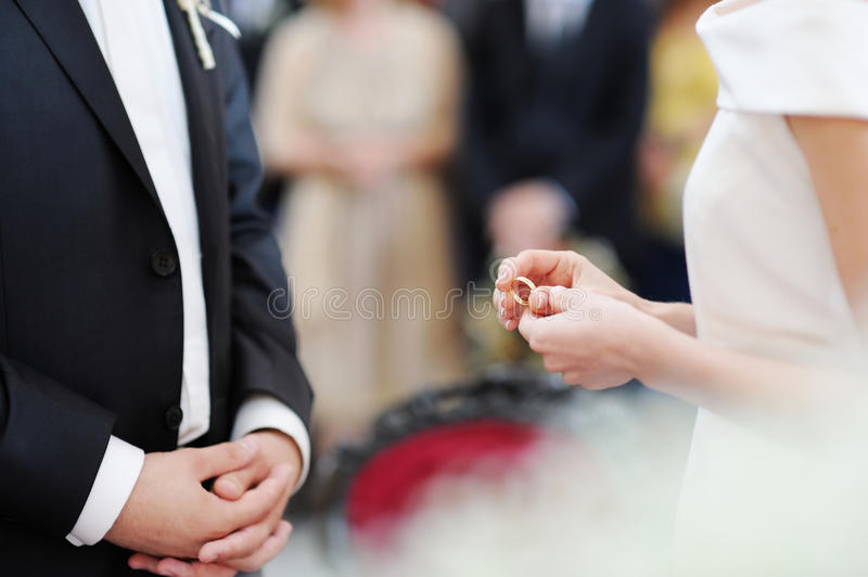 Bride putting a ring on groom s finger