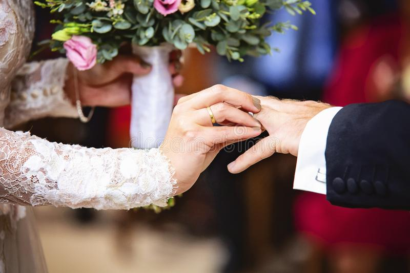 Bride putting a wedding ring to her groom finger royalty free stock photography