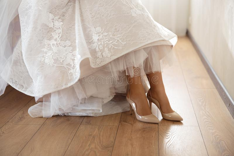 Bride putting on wedding shoes at home where she`s getting ready - Wearing white dress in a bright room with wooden royalty free stock image