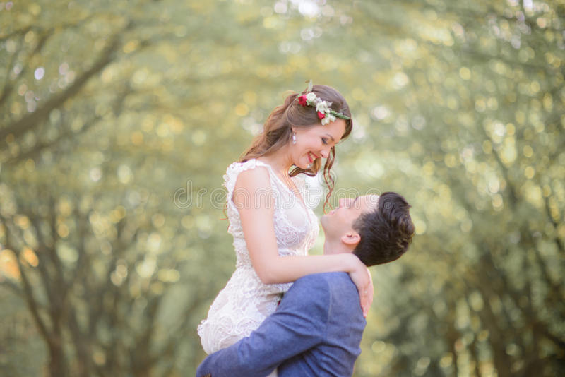Bride in red wreathe smiles to a groom while he holds her up.  stock photos