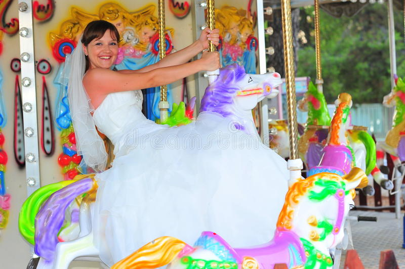 Bride riding the carousel stock image