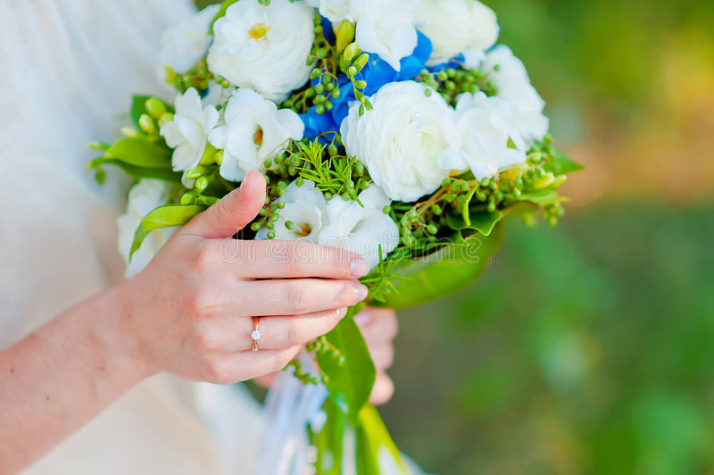 Bride with a ring holding a wedding bouquet of blue hydrangea fl. Owers stock photography