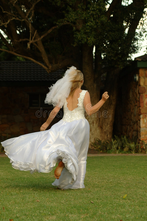 Bride running away. A beautiful caucasian barefeet bride in her white wedding dress being scared and running home and away from the wedding in the park outdoors stock images