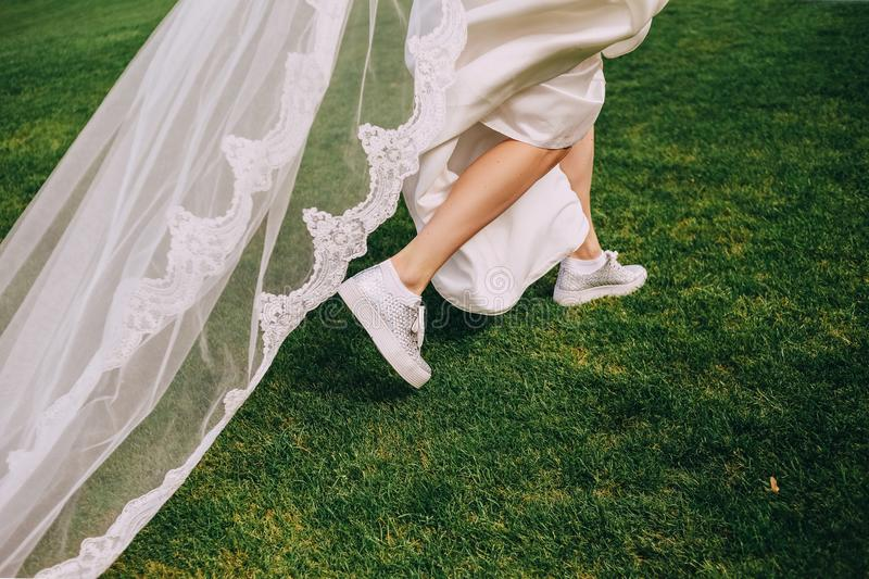 Bride run dress sneakers grass spring stock photography