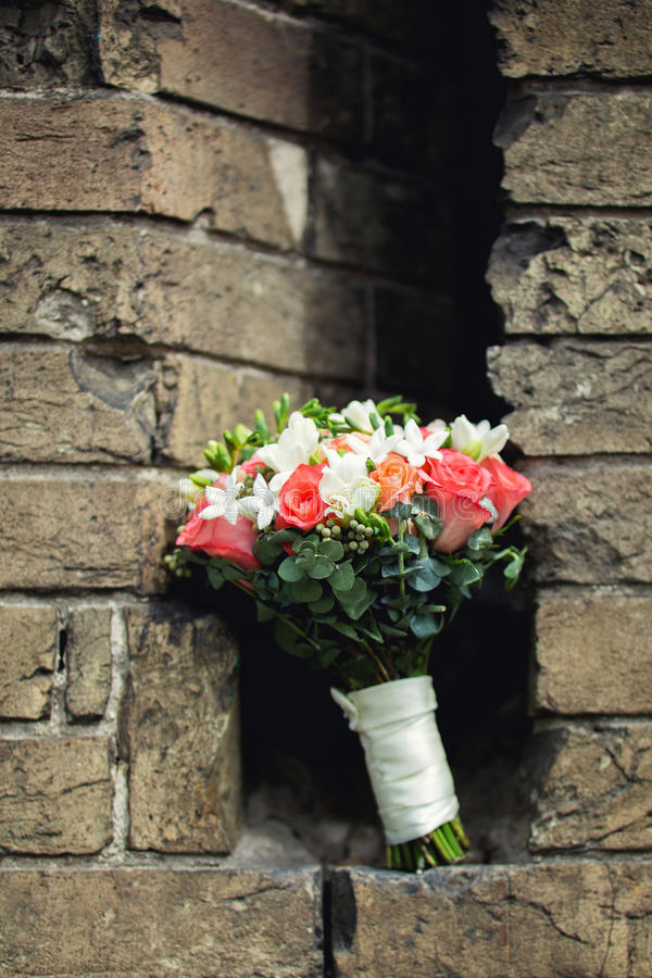 Bride's bouqet on the background of bricks. Bride's bouqet of roses and freesias on the background of brown bricks royalty free stock photos