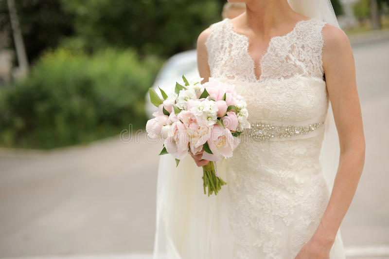 Bride's Bouquet of Pink Peonies. Bride holding her wedding bouquet of peonies stock image