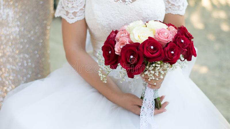 The bride`s bouquet, with red roses, white dress and natural white light royalty free stock images