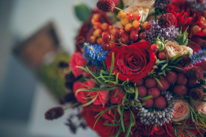 Bride`s bouquet with red roses, white roses, berries and green leaves stock image