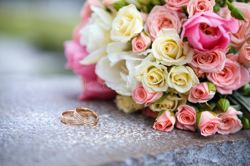 The bride`s bouquet of roses and wedding rings royalty free stock photography