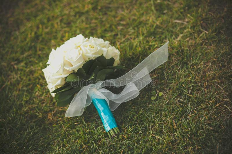The bride`s bouquet of white roses and green leaves, beautifully decorated with blue and white satin ribbon, lies on the grass on stock images