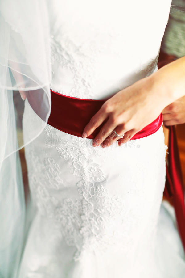 Bride's delicate hand holds a red satin belt on a wedding dress. A stock photography