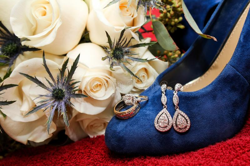 Bride`s Engagement Ring Resting on her Blue Suede Wedding Shoes stock photos