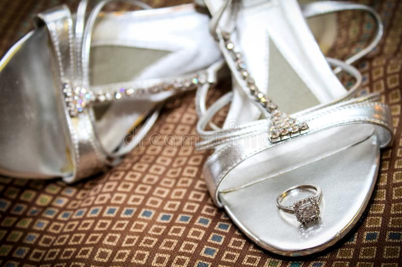 Bride`s Engagement Ring Resting on her Wedding Shoes.  royalty free stock photos