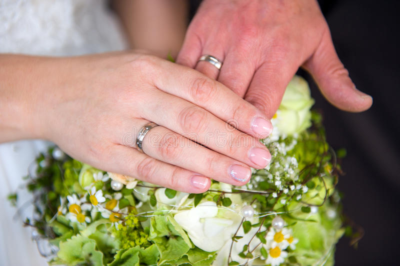 Bride's and grooms hand on flowers. Bride's and grooms hand with rings on flowers stock photos