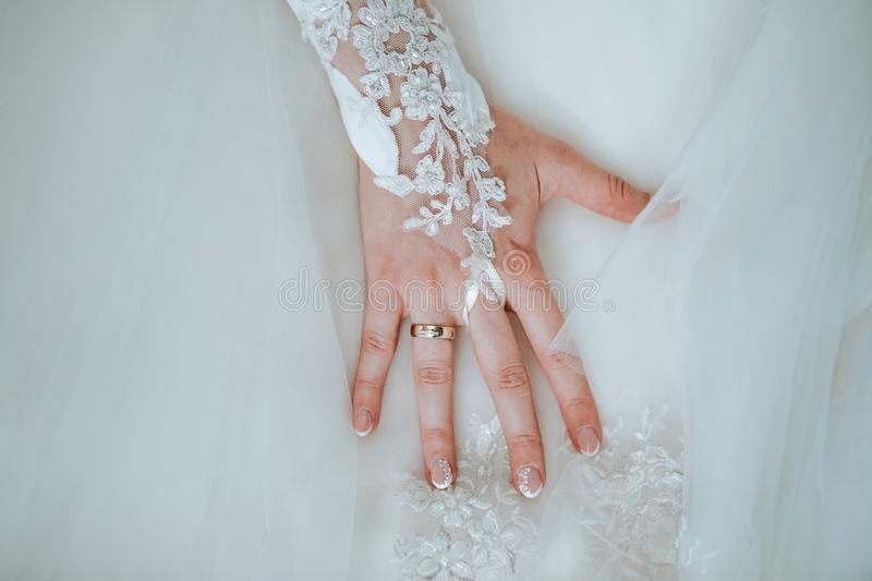 Bride`s hand on her wedding dress with the ring royalty free stock photos
