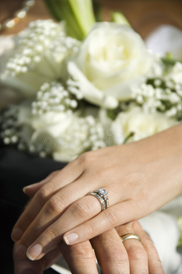 Bride's hand on top of groom's. stock photo