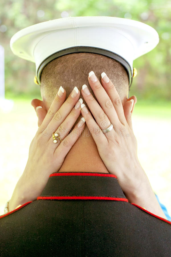 Bride's hands on back of soldier's head in embrace. royalty free stock photo