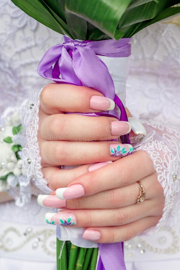 Bride`s hands holding a wedding bouquet. Fine manicure bridesmai. D stock images