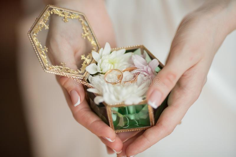 Wedding rings in jewelry box, romantic vintage style. Bride`s hands holding wedding rings in jewelry box, romantic vintage style royalty free stock images