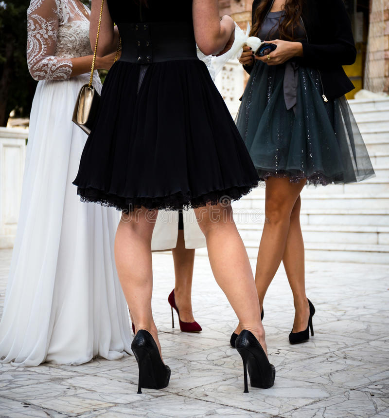 Bride`s and her friends legs. Bride`s and her female friend`s legs outdoor stock photography