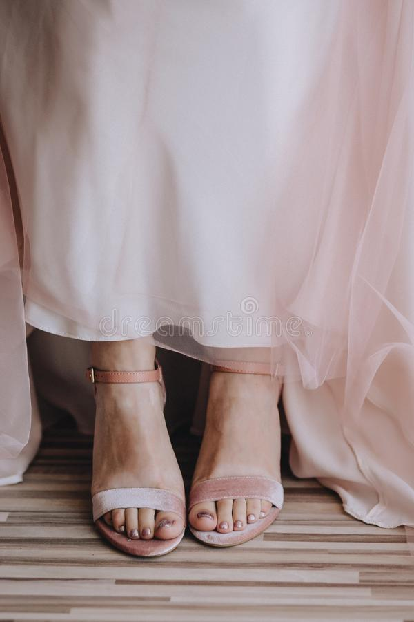 Bride`s legs close-up in velvet pink shoes and pink wedding dress transparent fabric royalty free stock photography