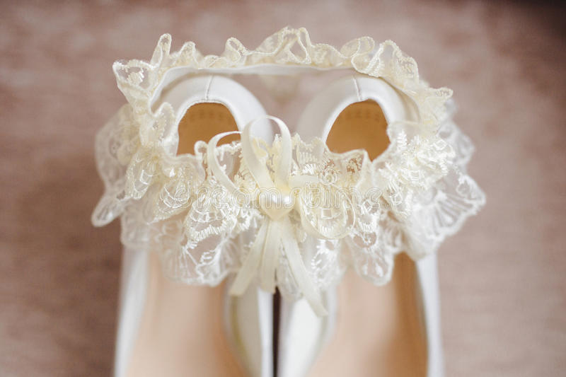 Bride`s shoes with a garter. Bride fees. bride`s shoes with a garter royalty free stock images
