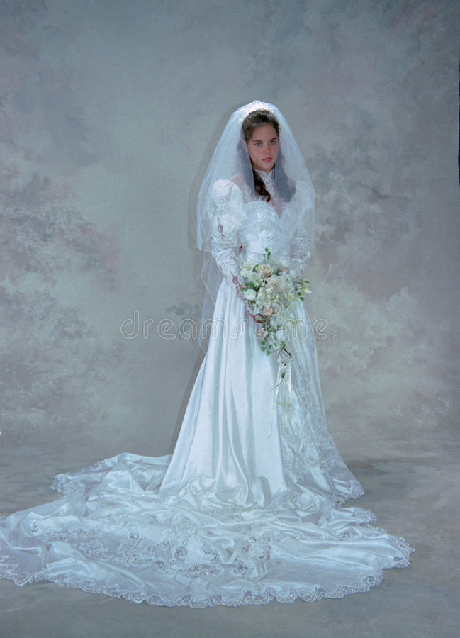 Bride in a Serious Moment. Formally posed bride appears lost in deep thought. Full length view, bridal gown with long train, beads, lace and all the trimmings stock photo