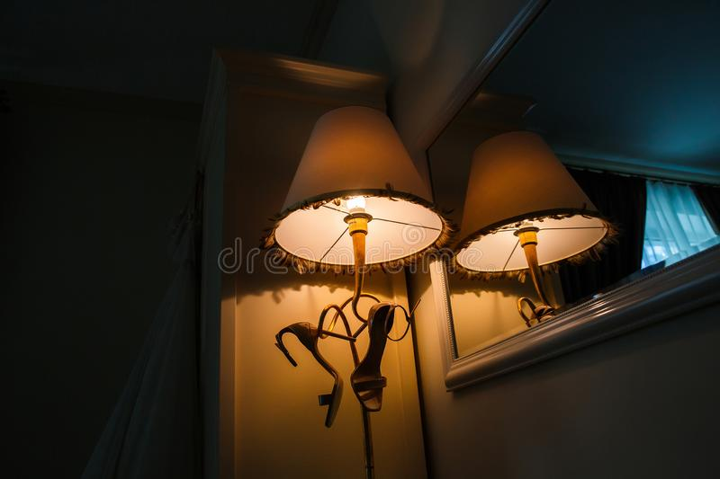 Bride shoes are hanging under the lampshade in the hotel room stock images