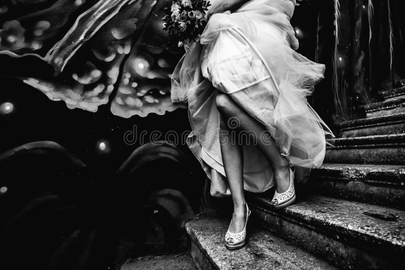 A bride in shoes runs up the stairs with a graffiti wall, holding a wedding dress in black and white stock photo