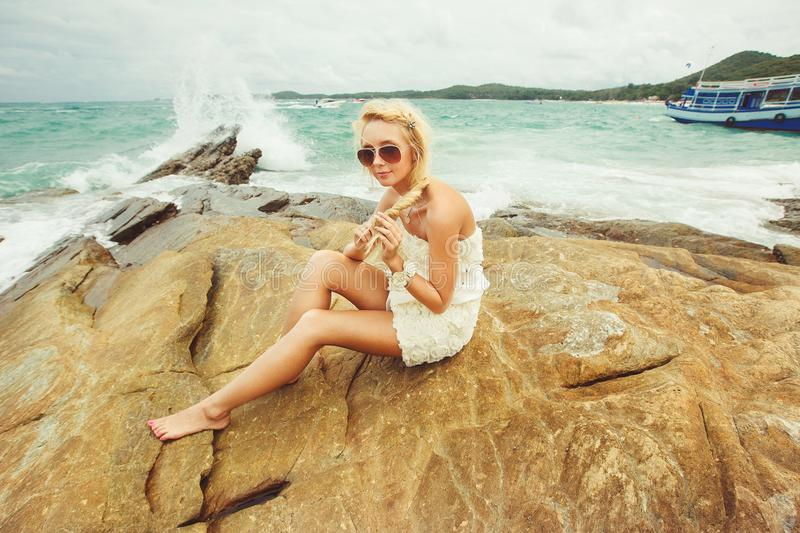 Bride in short wedding dress on the rocky beach. young beautiful woman in wedding day. stock photo