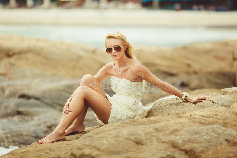 Bride in short wedding dress on the rocky beach. young beautiful woman in wedding day. royalty free stock photo