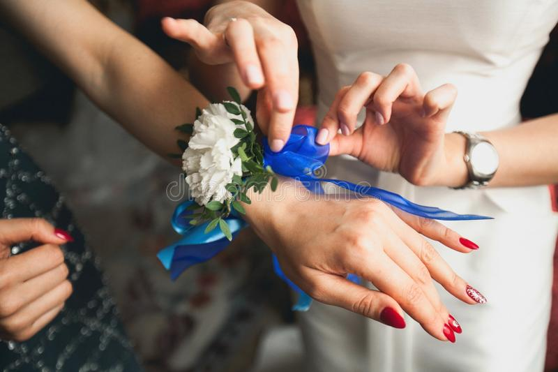 The bride shows her friend a boutonniere on hand, close-up. Bride`s morning, wedding day stock photo