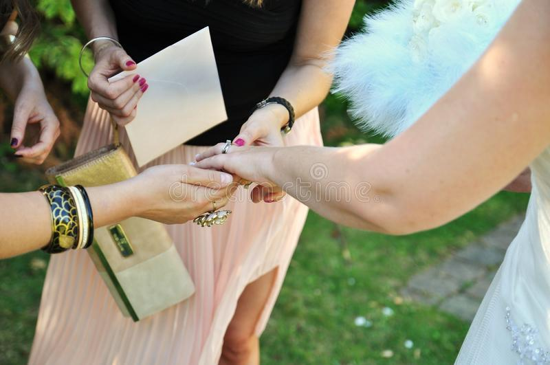 Bride shows her new wedding ring to female friends stock images
