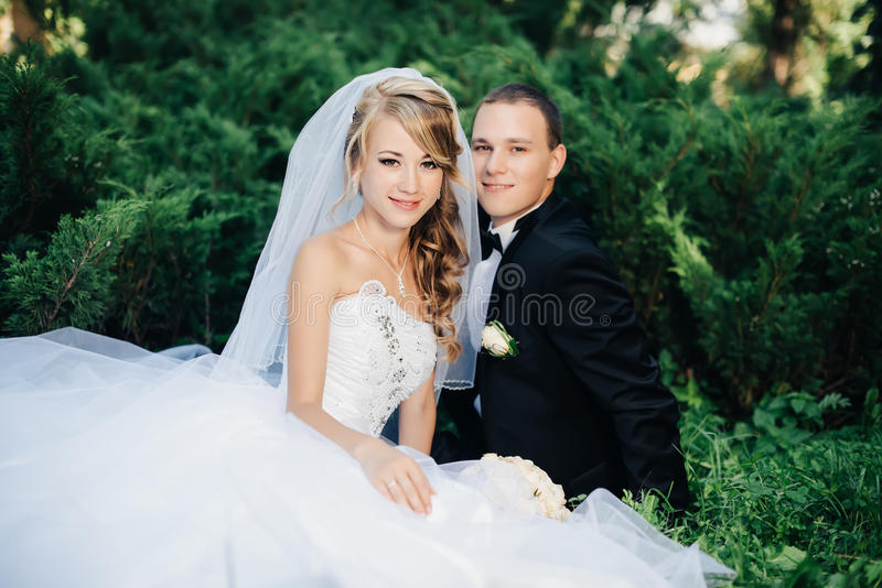 Bride sit together with groom on green grass park. Wedding, beautiful young bride sit together with groom in love on green grass kissing, park summer outdoor royalty free stock images