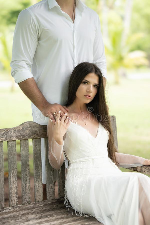 The bride sits on a bench, while the groom stands behind and holds her by the shoulders stock image