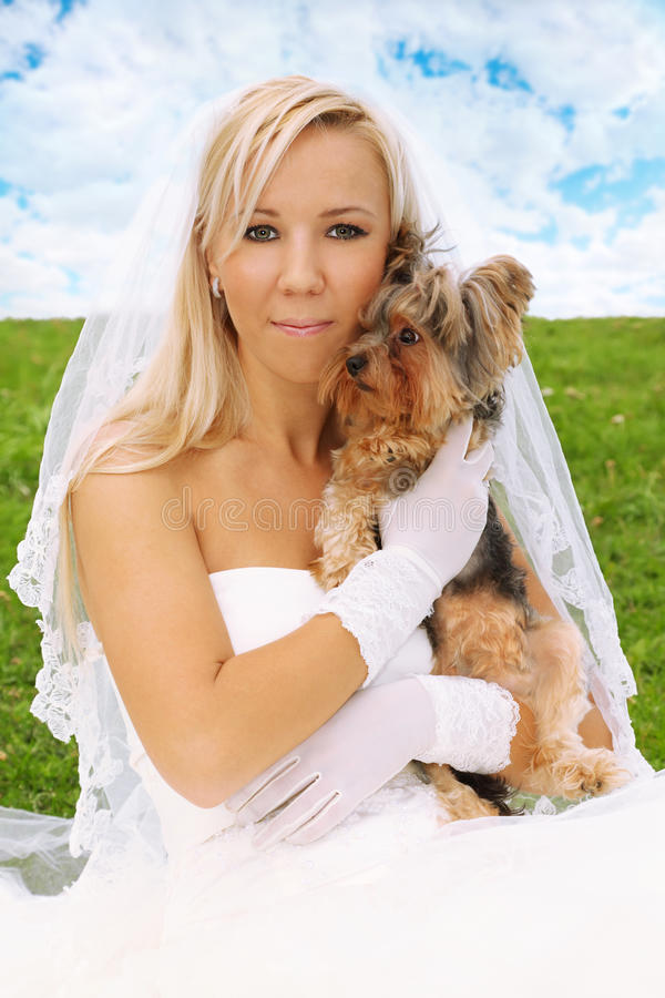 Bride sitting on green grass and keeps small dog