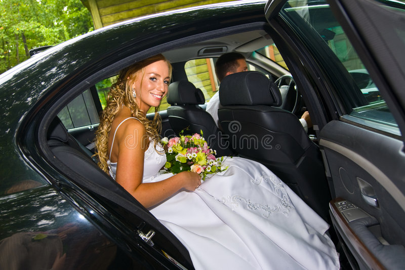 Bride sitting in a limousine. Bride sitting in a black wedding limousine royalty free stock image