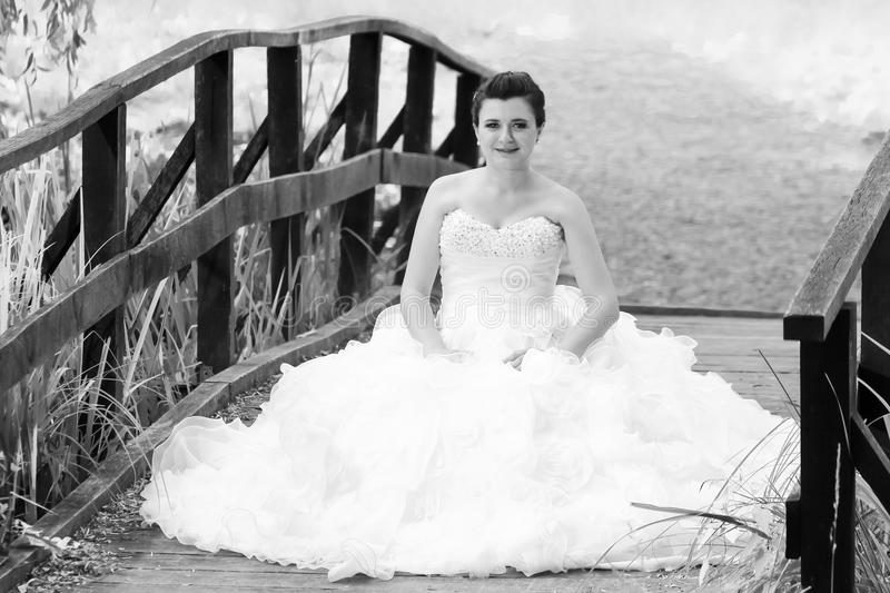 Bride sitting on wooden bridge black and white. A bride in wedding dress posing by sitting on a wooden bridge in nature and looking at camera royalty free stock images
