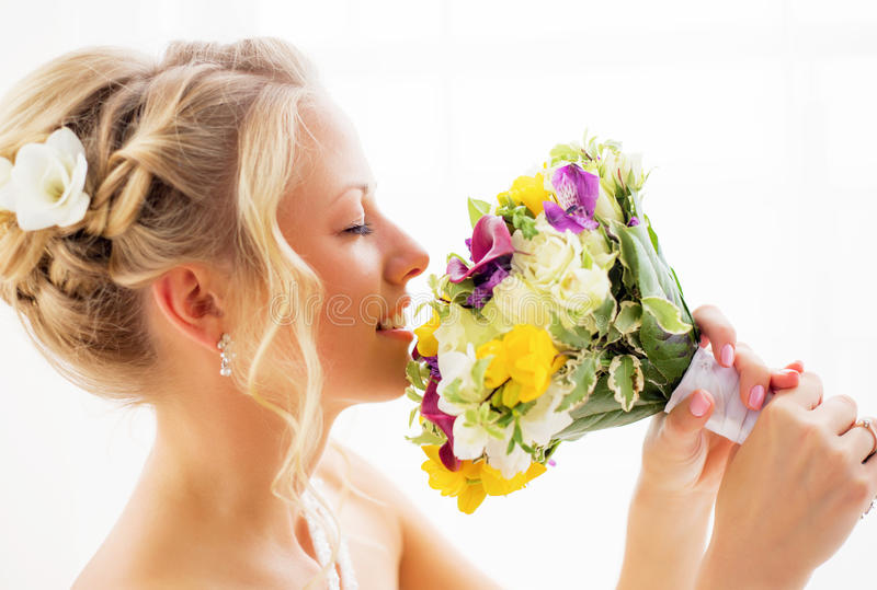 Bride smelling her wedding flowers stock photos