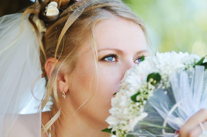 Bride smelling wedding bouquet stock image