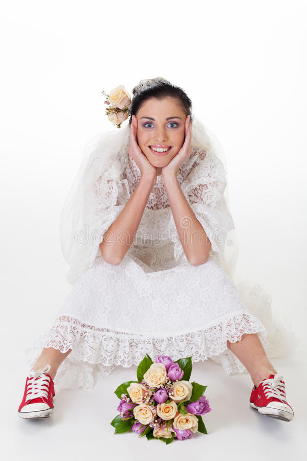 Bride in sneakers. Smiling bride in sneakers looking at camera stock photography