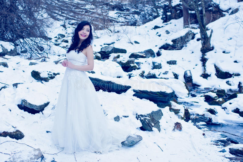 Bride on the snow. Beautiful girl stand on the snow field near a stream