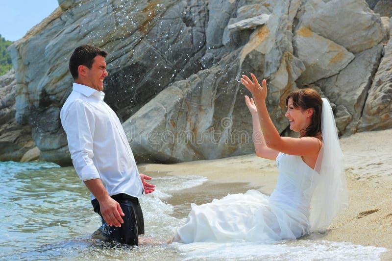 Bride Splashing Groom With Sea Water Stock Photos